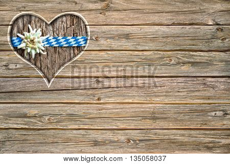 wooden oktoberfest board with heart shaped cut out, bavarian flag and edelweiss
