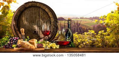 Barrel with glass of red wine and cheese on vineyard