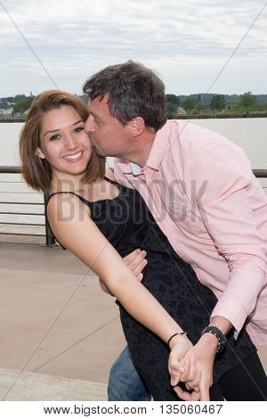 Man And Woman On The River Bank Embraces, Kisses