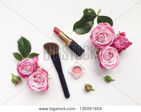 Decorative flat lay composition with cosmetics and flowers. Flat lay top view on white background