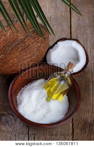 Coconut oil and coconut flakes on old wooden background.Selective focus