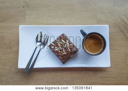 Chocolate brownies on plate and coffee mug, on wood table