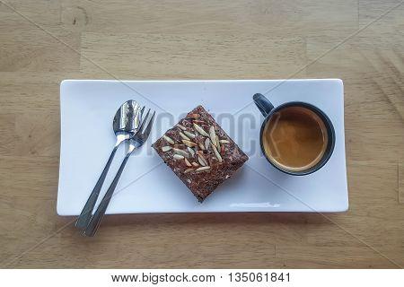 Chocolate brownies on plate and coffee mug, on wood table
