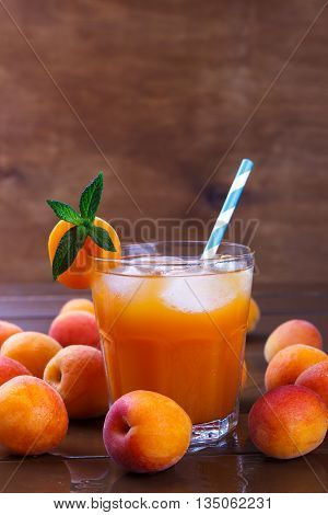 Fresh apricot juice with ice on old wet brown wooden table, selective focus