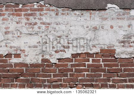ancient texture of an old brick wall with destroyed plaster for background in vintage style and for old wallpaper