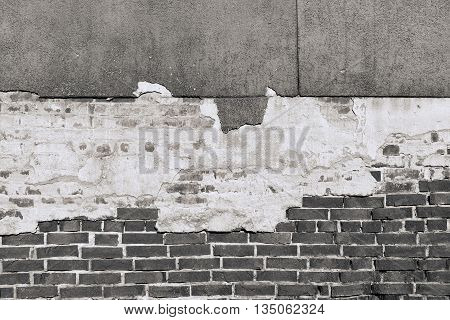 ancient texture of an old black brick wall with destroyed plaster for background in vintage style and for old wallpaper