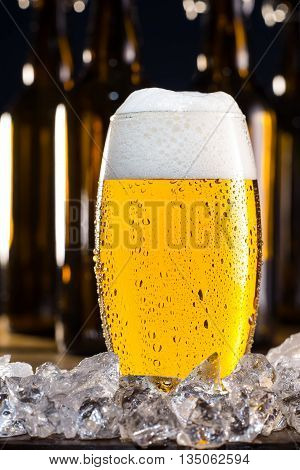 Frosty glass of beer with ice cubes and bottles on background