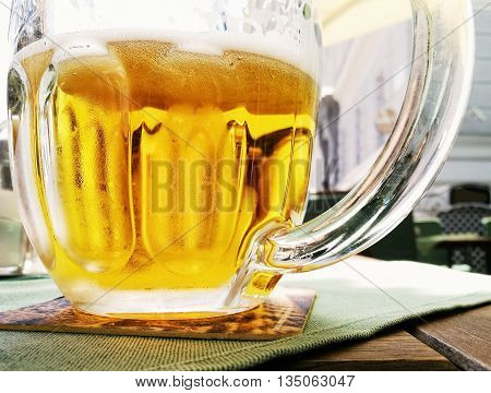 Glass of light beer. Tasty refreshment. Alcoholic drink. Glass cup on the tray. Lager beer.