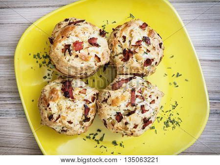 Delicious muffins stuffed with ham and cheese on the yellow plate. Refreshments for guests. International cuisine. Festive food. Tasty muffins. Food theme.