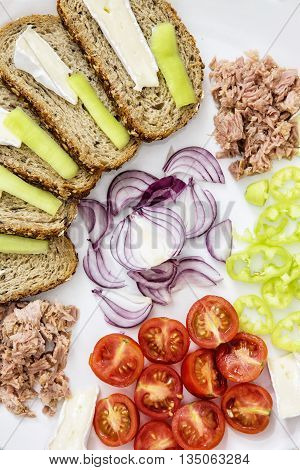 Sliced whole wheat bread with cheese paprika tuna onion and cherry tomatoes on the plate. Food theme. One portion. International cuisine.
