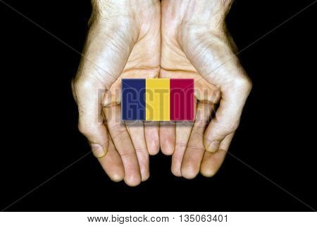 Flag of Chad in hands isolated on black background.