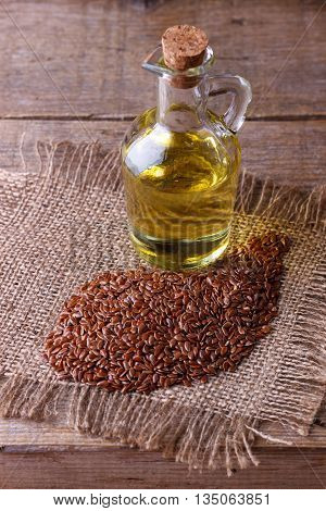 Linseed oil and flax seeds  on wooden background, selective focus