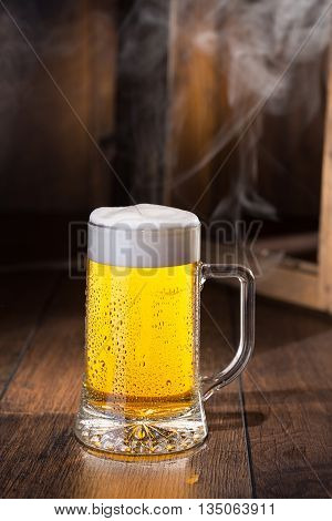 Frosty glass of beer, wood and smoke on background