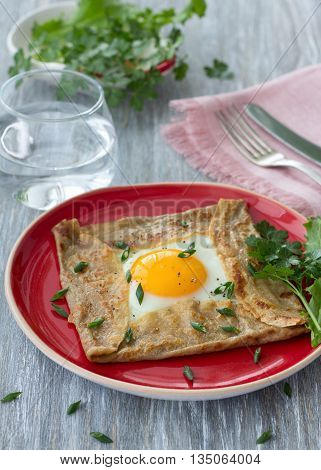 Homemade buckwheat pancakes with egg and cheese on the wooden table