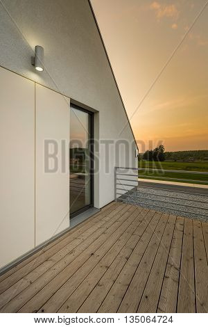 Spacious villa terrace with silver railing and wooden flooring