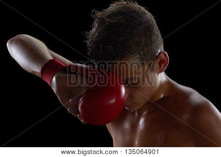 Young boy athlete boxer or kickboxer gloves after losing or training. Black background.