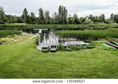 Nature Reserve Landscape. Several boats on the Coast of the River. Bulrush and Spring Trees reflecting on the River.