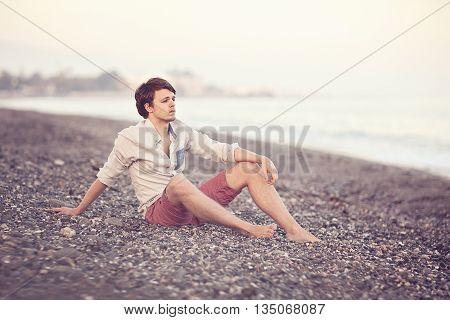 portrait of a cute teen sitting on the beach .soft evening light.