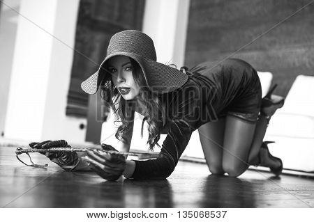 Sexy woman kneeling on floor in hat with whip black and white