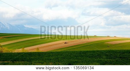 Farmer plowing the field. Cultivating tractor in the field. Snow mountain in background