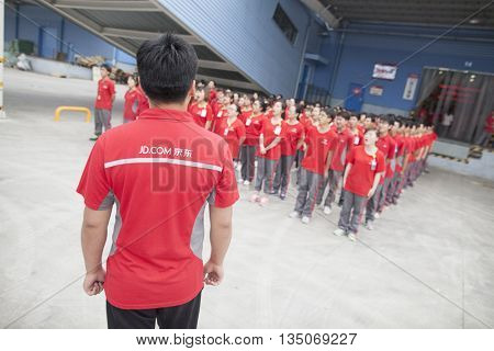 Gu'an, China - June 14, 2016: JD.com staff receiving instruction from manager at Northeast China based Gu'an warehouse and distribution facility