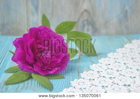 Pink rose flower on wooden table and crochet, rustic background. Selective focus, tender romantic background. Place for text, decoration with rose. Design for greeting card, Valentine's day, birthday