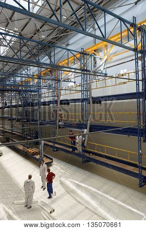 ST. PETERSBURG, RUSSIA - MAY 24, 2016: Workers in the workshop for production of ship hulls of composite materials at Sredne-Nevsky shipyard. The shipyard used composites since 1963