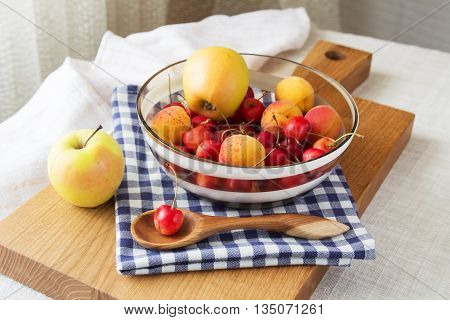 Composition of fruits and berries. Reason for the longevity is apples, cherries, apricots. Fruits and berries in a bowl on a checkered napkin on the table. Fruits and berries on a wooden cutting board