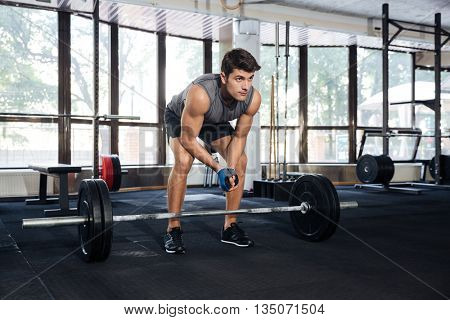 Muscular handsome man lifting barbell at gym