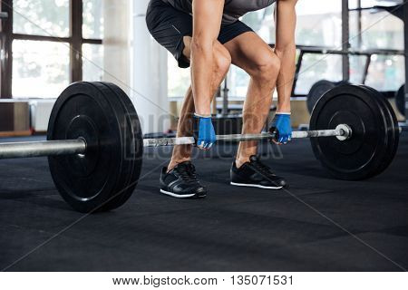 Cropped image of a fitness man lifting heavy barbell at gym