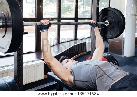 Portrait of a fitness man workout with barbell on the bench at gym