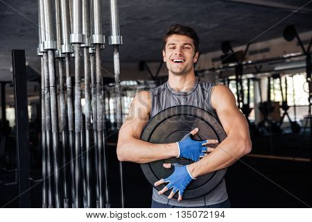 Young handsome smiling bodybuilder guy prepare to do exercises with barbell in a gym