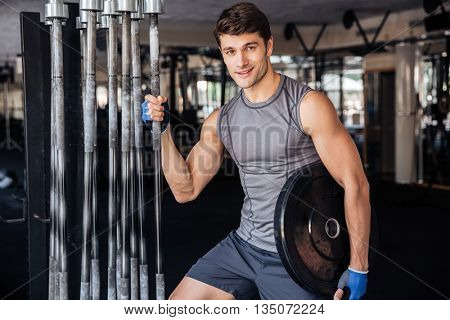 Young handsome bodybuilder guy prepare to do exercises with barbell in a gym