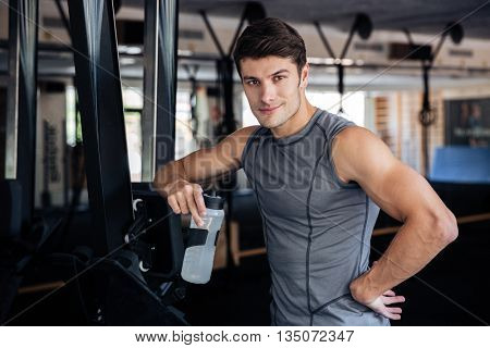 Smiling sports man holding bottle with water and resting in the gym