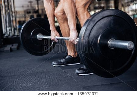 Cropped image of a muscular fitness healthy man lifting heavy barbell at the gym
