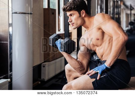 Portrait of a male muscular young bodybuilder workout with dumbbell in fitness gym