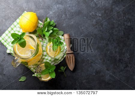 Lemonade with lemon, mint and ice on stone table. Top view with copy space