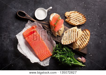 Sandwich toast with salmon cooking on stone background. Top view
