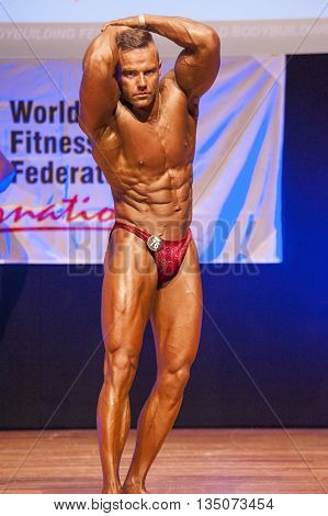 MAASTRICHT THE NETHERLANDS - OCTOBER 25 2015: Male bodybuilder flexes his muscles and shows his best abdominal and thighs pose at the World Grandprix Bodybuilding and Fitness of the WBBF-WFF