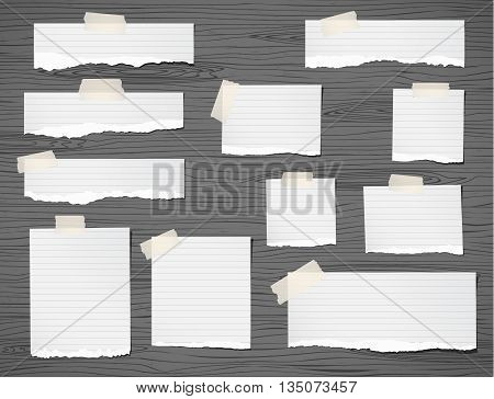 Pieces of ripped white note paper are stuck on dark wooden wall or tabletop.