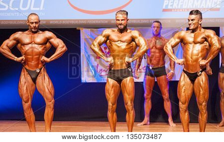 MAASTRICHT THE NETHERLANDS - OCTOBER 25 2015: Male bodybuilders flex their muscles and show their best lats spread pose at the World Grandprix Bodybuilding and Fitness of the WBBF-WFF