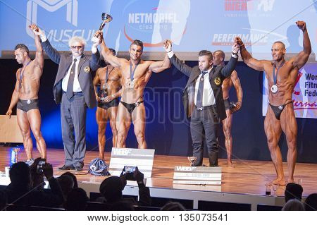 MAASTRICHT THE NETHERLANDS - OCTOBER 25 2015: Male bodybuilders celebrate their victory on stage with officials at the World Grandprix Bodybuilding and Fitness of the WBBF-WFF
