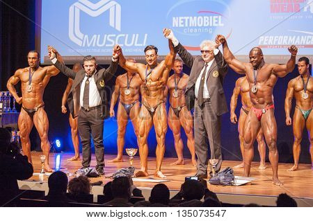MAASTRICHT THE NETHERLANDS - OCTOBER 25 2015: Male bodybuilders celebrate their victory with officials on stage at the World Grandprix Bodybuilding and Fitness of the WBBF-WFF