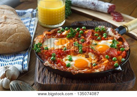 Eggs poached in tomato sauce and other vegetables served with bread