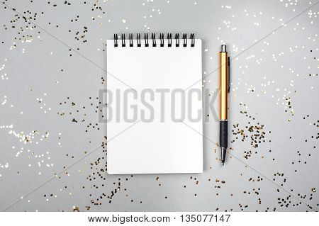 Paper note book with white pages and pen lying on festive background with little golden sparkles. Place for text.