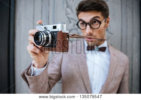 Happy funny stylish nerd holding camera outdoors