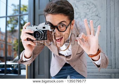 Happy funny young male photographer in round glasses showing ok sign and taking pictures outdoors