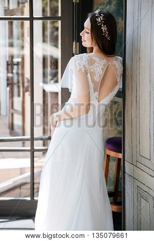 Back view of smiling charming bride in white dress and wreath
