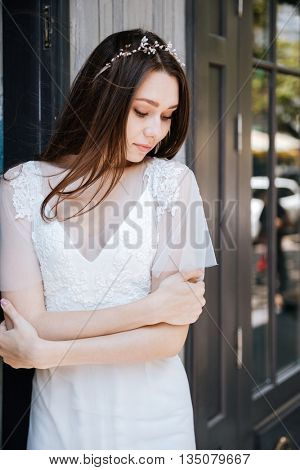 Portrait of tender young bride in white dress and wreath standing outdoors