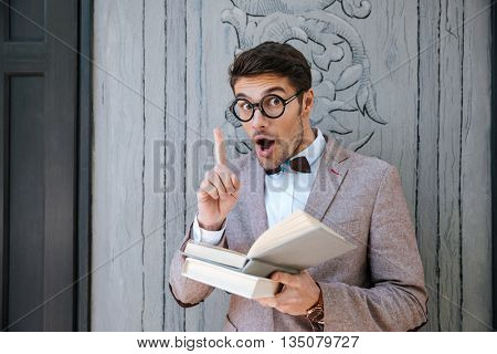 Inspired funny young man in round glasses reading book and having an idea